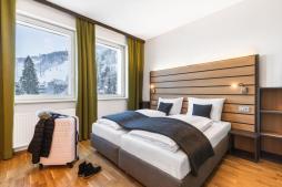doppelbett-doppelzimmer-jufa-hotel-schladming-koffer-1440x960